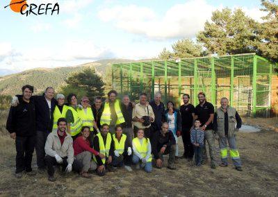 Foto de grupo de algunos voluntarios y trabajadores de GREFA que se lo curraron en el Día Internacional de los Buitres, delante del jaulón de aclimatación de buitres negros de Huerta de Arriba (Burgos).